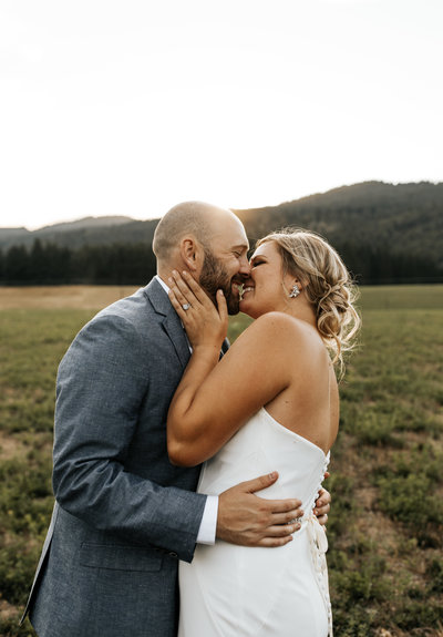couple shares a kiss in sunny field