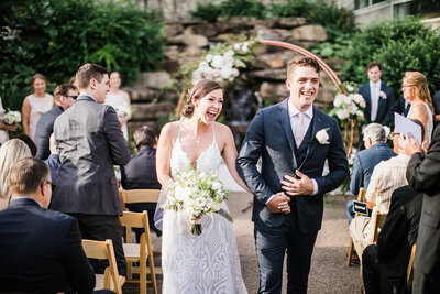 Bride and Groom Walk Up Aisle after outdoor wedding at Phipps Conservatory