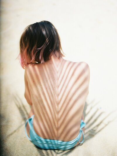 Shadows on the spine of a girl with pink tipped hair on the beach in a blue swimsuit for her boudoir session in Puerto Rico.