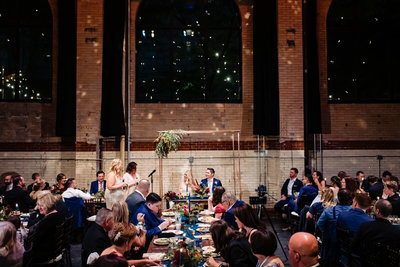 Wedding reception speeches with couple under unique arch with flower arrangement