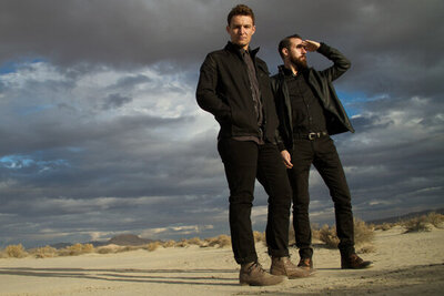 Portrait of music duo Polarcode standing in desert one member shielding eyes with hand big sky with clouds behind them