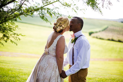 Bride and groom kiss under a tree at their Betsy's Barn wedding