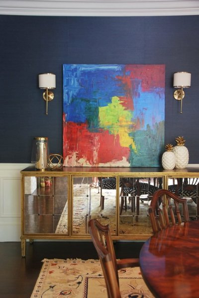 A gold and mirrored buffet and colorful abstract painting on a navy wall.