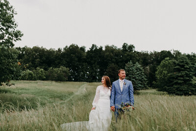 bride and groom holding hands while standing in field