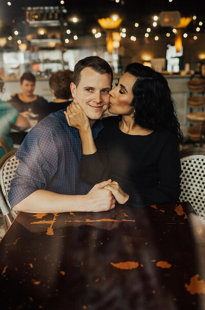 woman kissing man on cheek while sitting at table