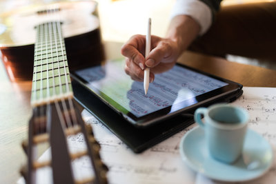 Close-up of a guitar, coffee cup and Nic's hand making music notations on an ipad