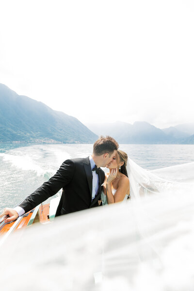 couple kissing on a boat in lake como