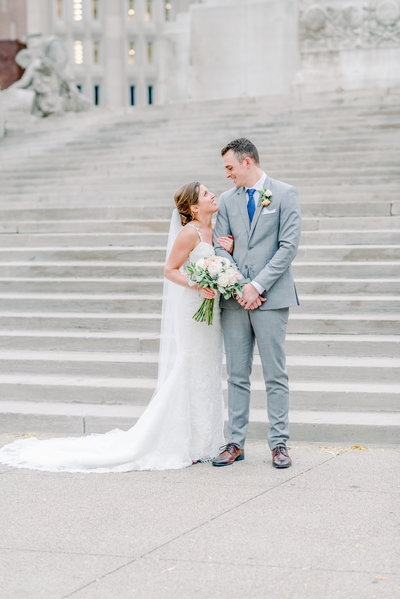 JPS Regions Tower Wedding - Couple poses for their wedding portraits on the steps of Monument Circle in downtown Indianapolis