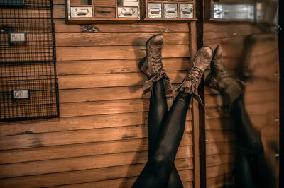 BYOBrand Podcast Host Hannah Ellaham's Combat Boots against wall with black shiny leggings