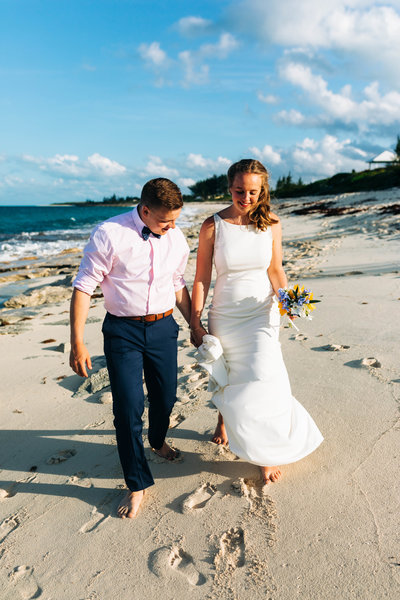 a bride and groom walking down the beach during their destination elopement