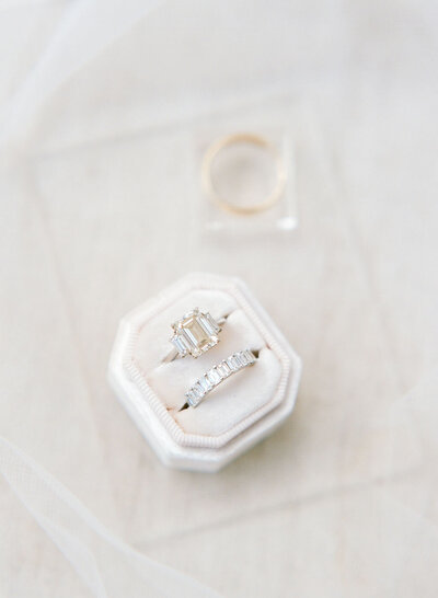 Diamond engagement ring and wedding band in white ring box.