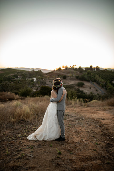 Bride and groom hugging in the middle of a golden field during sunset