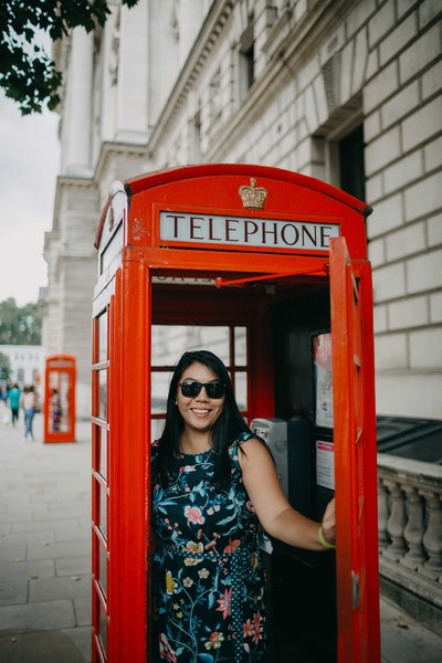 Headshot of Diana Wei Fang of The Finer Points. She is wearing a dark floral sleeveless dress and black sunglasses. She is standing inside of a British telephone booth, holding the door open with her left arm.