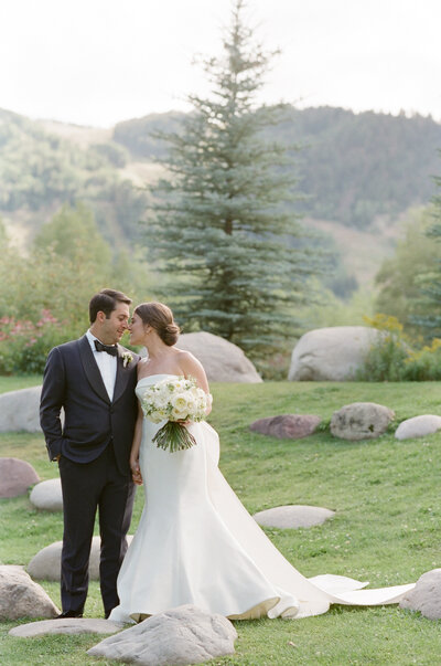 Bride and groom look at each other in a field with boulders around them