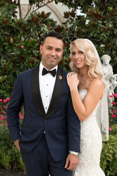 Classic and timeless wedding photo of bride and groom  in a rose garden at a winery with a greek statue in the background. The groom in a handmade fitted blue tux and the bride looking like a 1950 's movie star with bold eyeshadow and lipstick and long wavy blond hair.