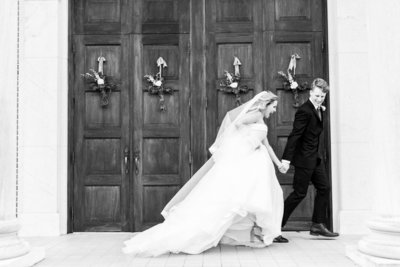 Bride and Groom running in front of the church together in a black and white motion blur image.