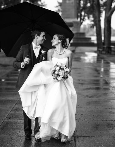 bride and groom smiling at each other walking under an umbrella  around Perry Monument on Presque Isle State Park