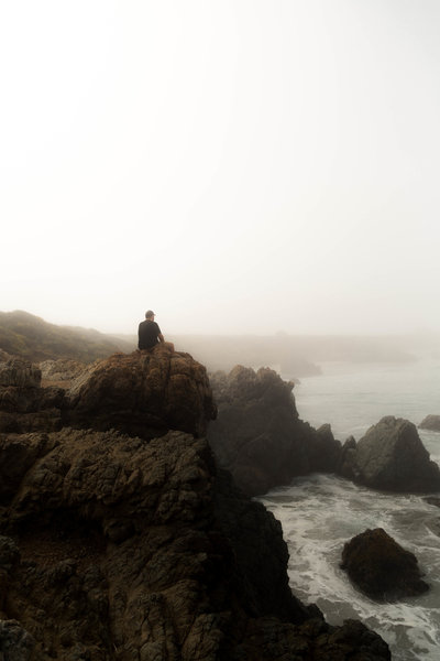 ATlanta Wedding Photographer Grant Bingham sit on cliff looks at ocean