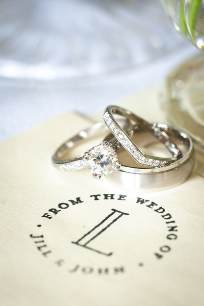Close up of wedding rings stacked next to couple's monogram
