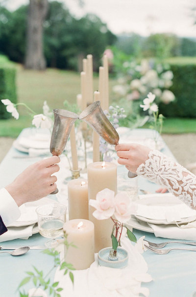 Couple cheersing with champagne goblets on outdoor table setting