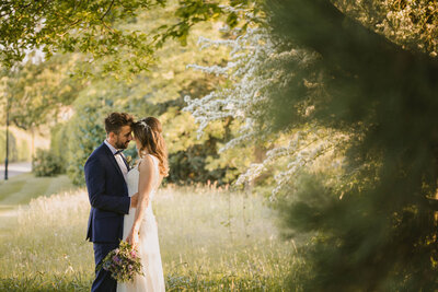 Bride and groom in wild grass at Highfield Park on their wedding day
