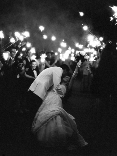 Epic black and white sparkler exit portrait of bride and groom with bride raising her bouquet into the air!