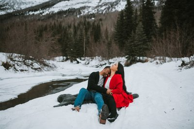 couple sitting in the snow laughing together with eagle river mountains behind them