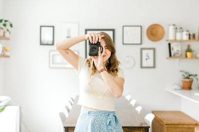 Woman taking picture in bright dining room