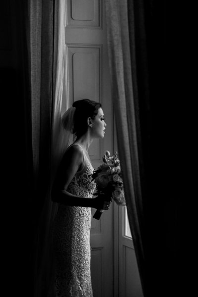 Bride looking out window holding a bouqet