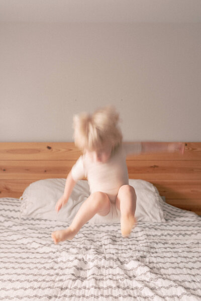 Little boy mid-air as he jumps on the bed