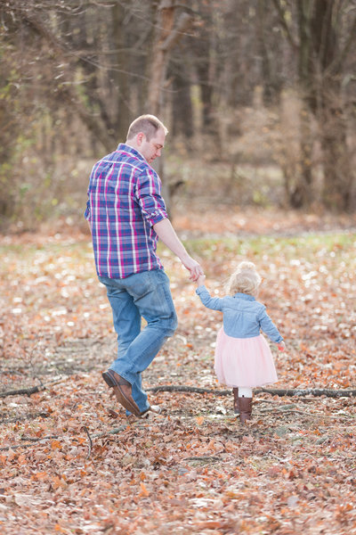 Father in plaid shirt walks through a field of leaves holding his young daughters hand
