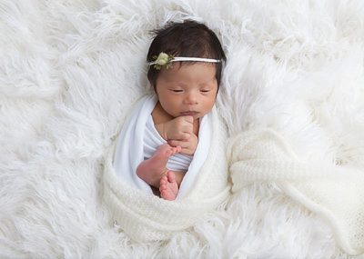 newborn baby girl on white fur
