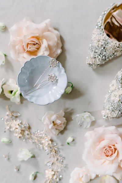 bridal jewelry flat lay with roses and embellished shoes by wedding photographer in dallas Catie ann photography