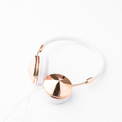 white and gold headphones on white background