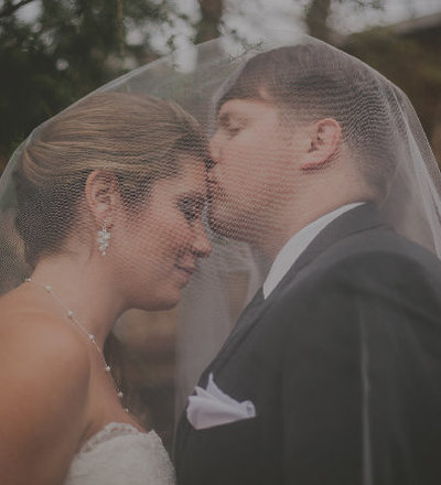 Groom kisses Bride on forehead after wedding at the Old Cigar Warehouse in Greenville SC