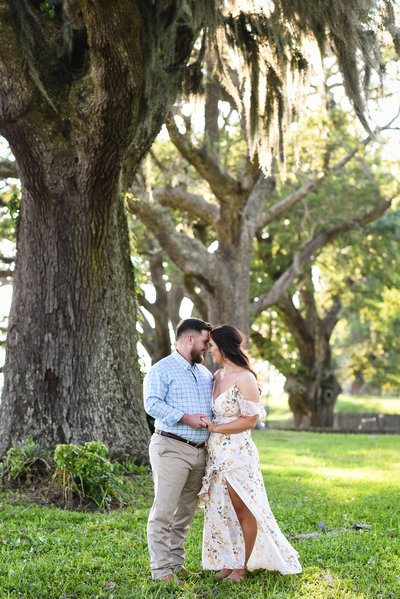 Beautiful engagement Photography: Couple in front of oaks with Spanish moss in Ocean Springs, Mississippi