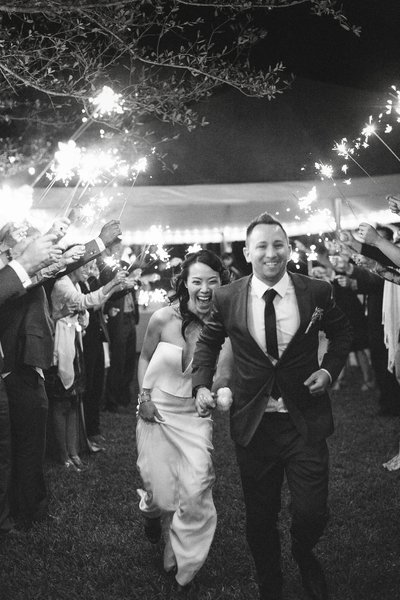 bride and groom race through a tunnel of sparklers at their intimate wedding at BMR Stables in Jupiter
