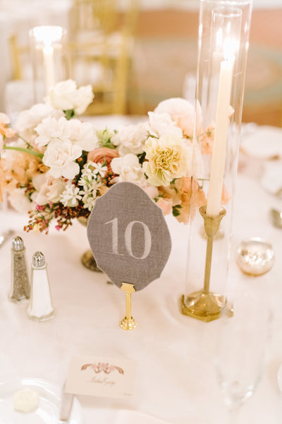 white and pastel colored floral centerpiece by roots floral design with brass candlesticks and a velvet table number at the brown hotel