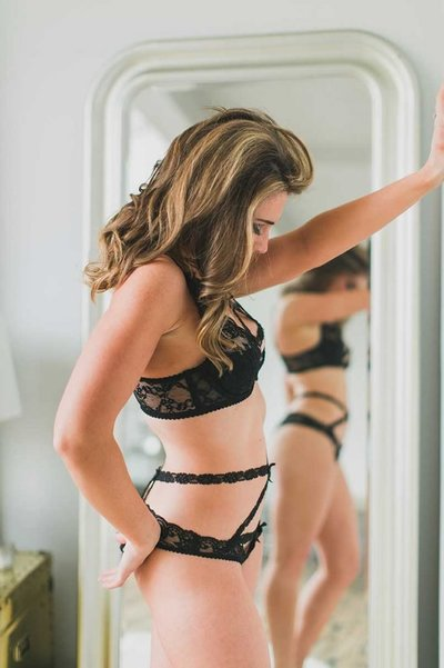 A romantic boudoir photo that captures a woman's reflection in the mirror.