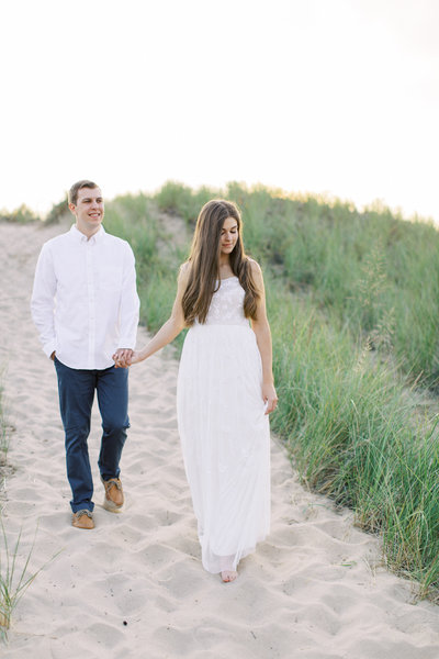 Engaged couple walking along Minnesota beach