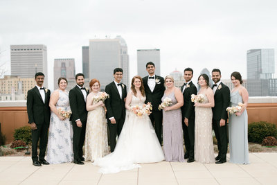 the wedding party standing on the balcony of the brown hotel looking over the city of louisville