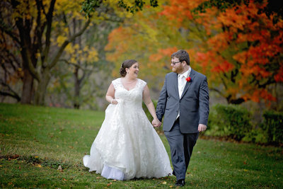 Bride and groom look at each other as they walk in the fall colors