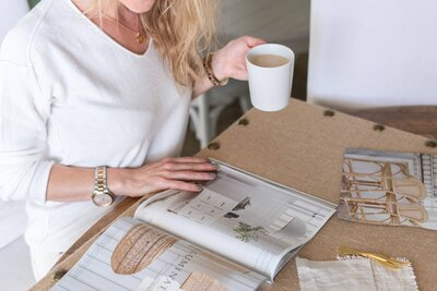 Woman looking at a magazine holding a cup of coffe on her left hand