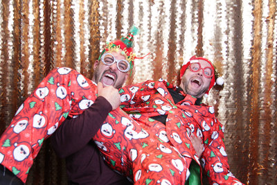 best christmas outfits and friends ever front of a photo booth