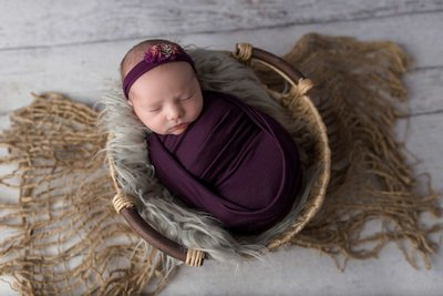 sleeping newborn swaddled in purple baby wrap in portrait studio