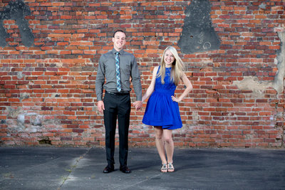 couple poses for engagement portrait in front of a brick wall in conway, south carolina
