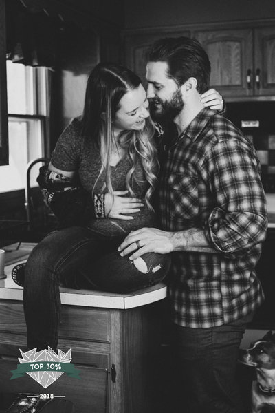 Couple standing in kitchen holding baby bump