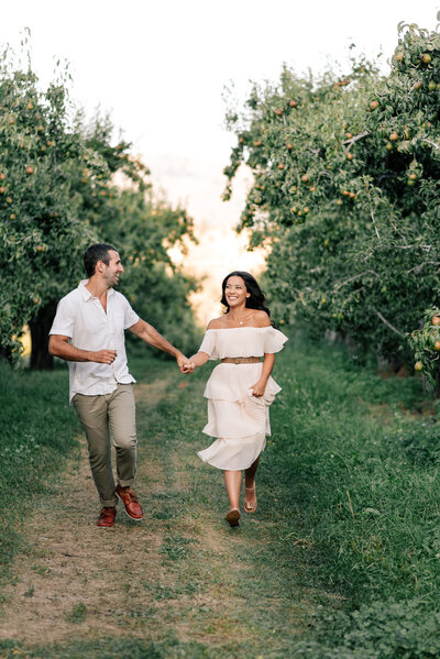 Couple running through an orchard during Leavenworth engagement session at Beecher Hill House