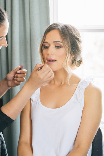 Bride getting professional makeup applied on her wedding day