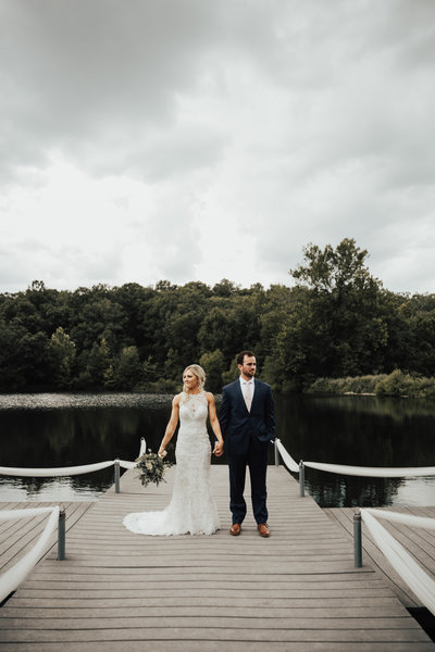 Bride and groom standing on a dock in front of a beautiful lake in Missouri before their intimate wedding.